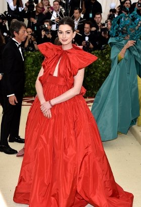 Anne Hathaway wears a full red dress on the red carpet for the 2018 met gala
